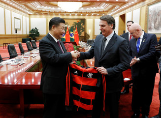 China's President Xi Jinping revives a gift from Brazil's President Jair Bolsonaro at the end of the signing ceremony at the Great Hall of the People in Beijing