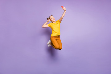 Full length photo of amazing lady jumping high holding telephone taking selfies showing v-sign symbol near eye wear yellow t-shirt pants isolated pastel purple background