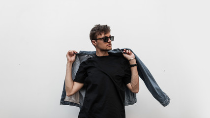 Cool modern young hipster man with a stylish hairstyle in sunglasses in a black T-shirt puts on a vintage blue denim jacket. Attractive urban guy posing near a white wall. Fashionable spring menswear.