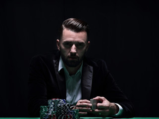 A wealthy man playing poker with the excitement in a casino.