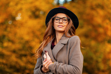 Portrait of attractive elegant young woman in stylish glasses in a trendy hat in an fashionable coat on a background of a trees with golden leaves in the park. Beautiful modern hipster girl outdoors.