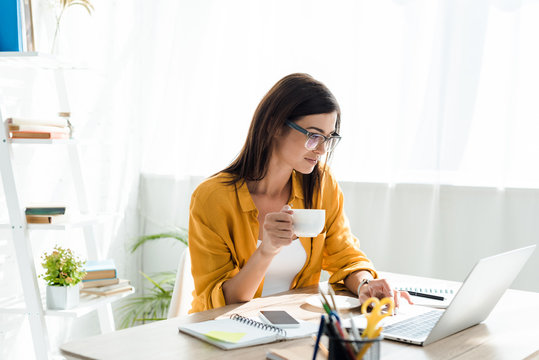 beautiful freelancer working on laptop with coffee cup in home office