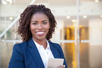 Happy joyful manager with tablet posing outside. Young African American business woman holding and embracing digital device, looking at camera, smiling. Gadget user concept
