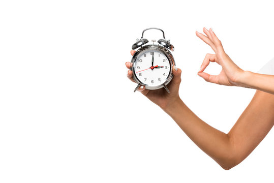 partial view of woman holding alarm clock, isolated on white