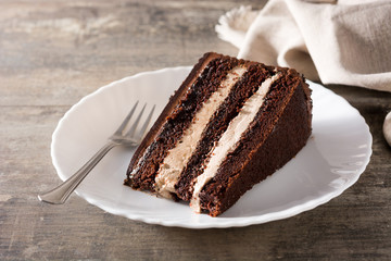 Chocolate cake slice on wooden table