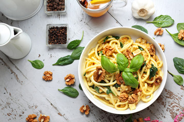 Pasta bucatini in a cream sauce with fresh spinach, garlic walnuts