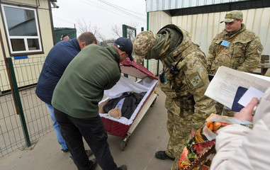 A serviceman inspects a coffin containing a deceased man being transported through a check point from the self-proclaimed Luhansk People's Republic to Ukrainian government-controlled territory for his funeral in Stanytsia Luhanska