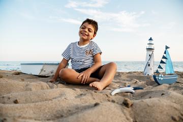 niño en la playa, sobre arena. jugando. sesión de fotos de verano.
