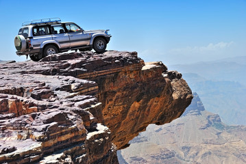 YEMEN - MARCH 13, 2010: Toyota Land Cruiser Off-road vehicle on the edge of a steep cliff over breakaway at plateau Bokur (800m high). Extreme mountain safari is one of the main local tourist attracti