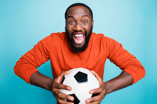 Portrait of cheerful excited mixed-race overjoyed ecstatic man holding ball rejoicing in goal of his favorite team isolated over blue vivid color background