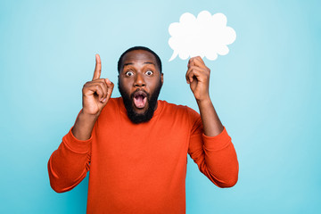 Photo of funny cheerful mixed-race man showing his forefinger up with amazement on face holding...