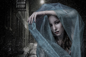 Beautiful mysterious young girl with pale skin and black tears. Portrait of the vampire woman with shawl on the nighty deserted street with falling first snow in Halloween