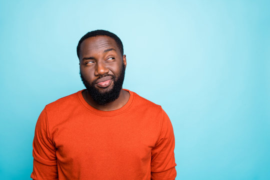 Photo of attractive dark skin guy looking tricky to empty space playful mood think over funny trick wear casual orange sweater isolated blue color background