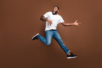 Full length body size photo of trendy stylish cheerful handsome guy running jumping playing guitar in air wearing white t-shirt casual jeans denim footwear isolated over pastel brown color background