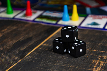 three black dice for a board game on the board