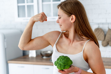 Strong woman with broccoli in the kitchen. Young healthy girl shows her strong hands.