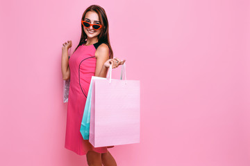 young beautiful woman, in pink dress and sunglasses, with shopping on pink background Wall mural