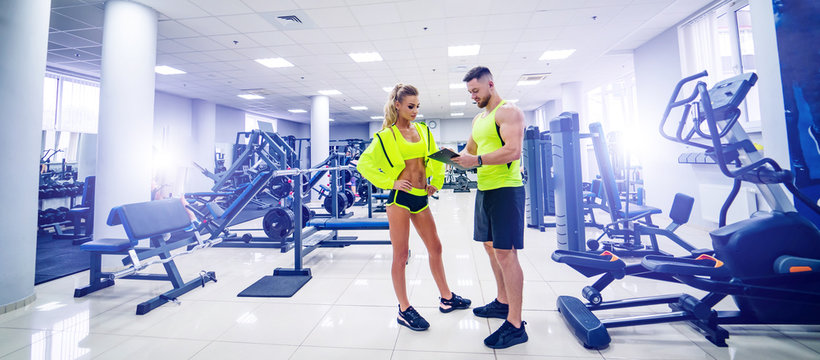 Trainer communicating with female client, creating her personal workout plan.