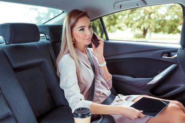 Beautiful woman car interior passenger, phoning, working road, tablet touch screen. Business VIP taxi rental car sharing city. Summer girl autumn city. Strict suit, long hair casual makeup.