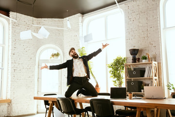 Young caucasian businessman having fun dancing break dance in the modern office at work time with gadgets. Management, freedom, professional occupation, alternative way of working. Loves his job. Wall mural