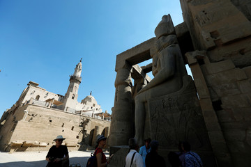 An Egyptian tour guide with his group is seen during Friday prayers near he Mosque of Abu El-Haggag, which was built inside the temple of Luxor