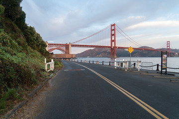Side View Of The Golden Gate Bridge With Leading Road And Mountains In The Early Morning Hours.