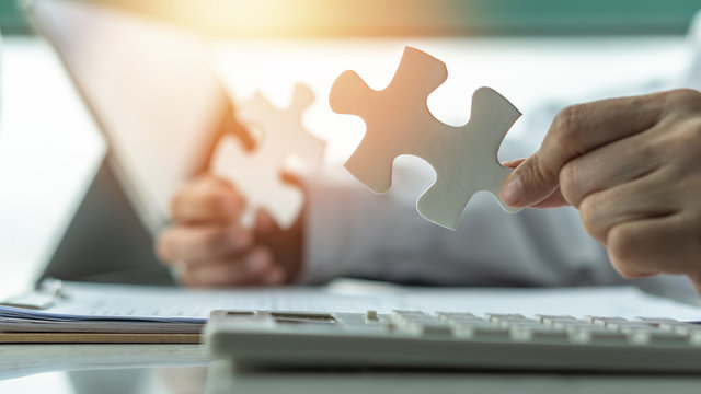 Business solution and strategy for corporate business success concept with jigsaw puzzle pieces in businessman hands finding problem solving idea and strategic planning
