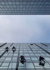 Window cleaners wash the exterior of an office building in Gdansk