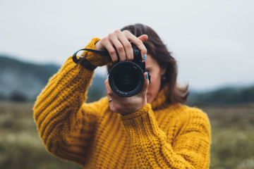 Wall Mural - photographer girl take photo on camera closeup on background autumn foggy mountain, tourist shooting nature mist landscape, hobby concept, copy space
