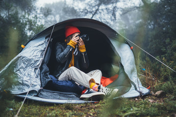 Wall Mural - photographer tourist traveler take photo on camera in camp tent in foggy rain forest, hiker woman shooting mist nature trip, trekking tourism, rest vacation concept camping holiday