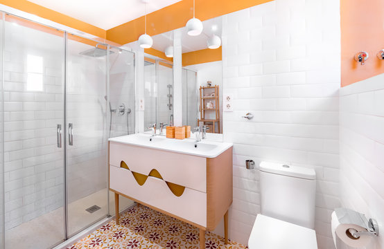 Young and trendy interior design. Modern and colorful bathroom with wooden cabinet.  Yellow and orange tiles.