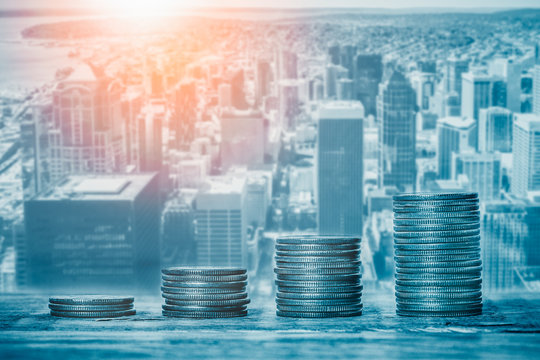 Stacks of coins with cityscape or skyline in the background. Financial growth, real estate sector prices, municipal budget or city funds, economy or banking concepts.