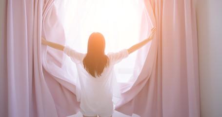 asian woman opening curtain