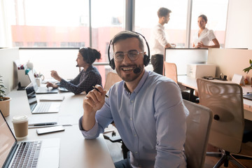 Millennial happy male call center agent looking into camera.