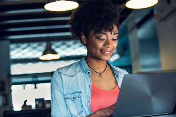 Smiling young businesswoman using laptop in office