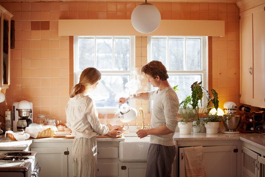 Husband and wife preparing tea in kitchen at home