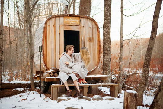 Couple romancing by sitting on steps by sauna vehicle in forest during winter