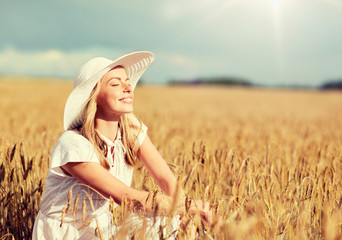 nature, summer holidays, vacation and people concept - happy young woman in white dress and sun hat enjoying sun on cereal field Fotoväggar