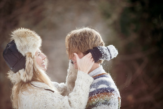 Side view of smiling romantic couple looking at each other while standing in forest during winter