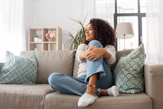 people, race, ethnicity and portrait concept - happy african american young woman sitting on sofa at home