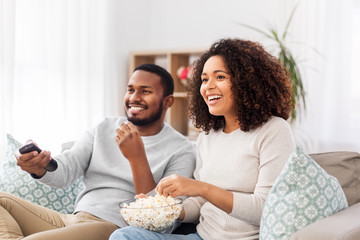 people and leisure concept - african american couple with popcorn watching tv at home