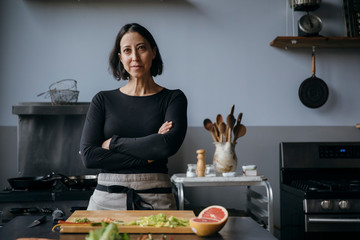 Portrait of confident female chef with arms crossed standing by table against wall in training class