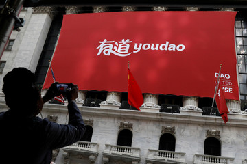 A woman photographs a banner for Youdao Inc. during the company's IPO at the NYSE in New York