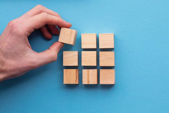 Hand choosing a wooden block from a set. Business choice concept