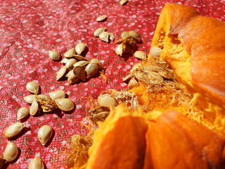 Broken pumpkin with seeds on the red surface. Close up, top view.