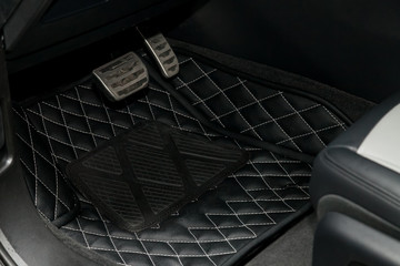 Clean black leather car floor mats with diamond stitching and gas pedals and brakes in the workshop for the detailing vehicle after dry cleaning