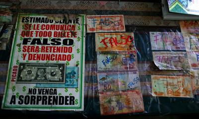 Counterfeit money is seen at the cash desk of the Villa Fatima coca market in La Paz