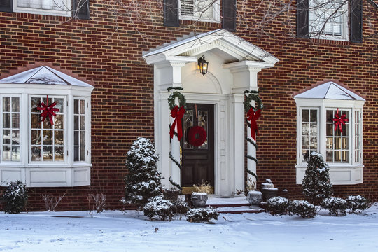 Entry and porch to traditional Georgian style brick house with columns and bay windows decorated for Christmas in the snow