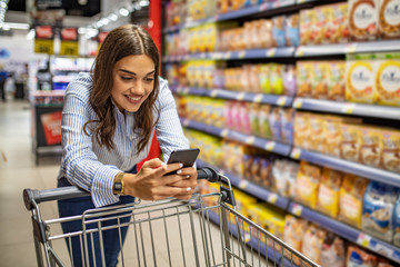 Cropped image of girl leaning on shopping cart, using a mobile phone and smiling. Woman buy products with her trolley at supermarket. Woman shopping in supermarket