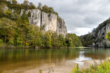 Danube river at Danube breakthrough near Kelheim, Bavaria, Germany in autumn with limestone rock formations and plants with colorful leaves